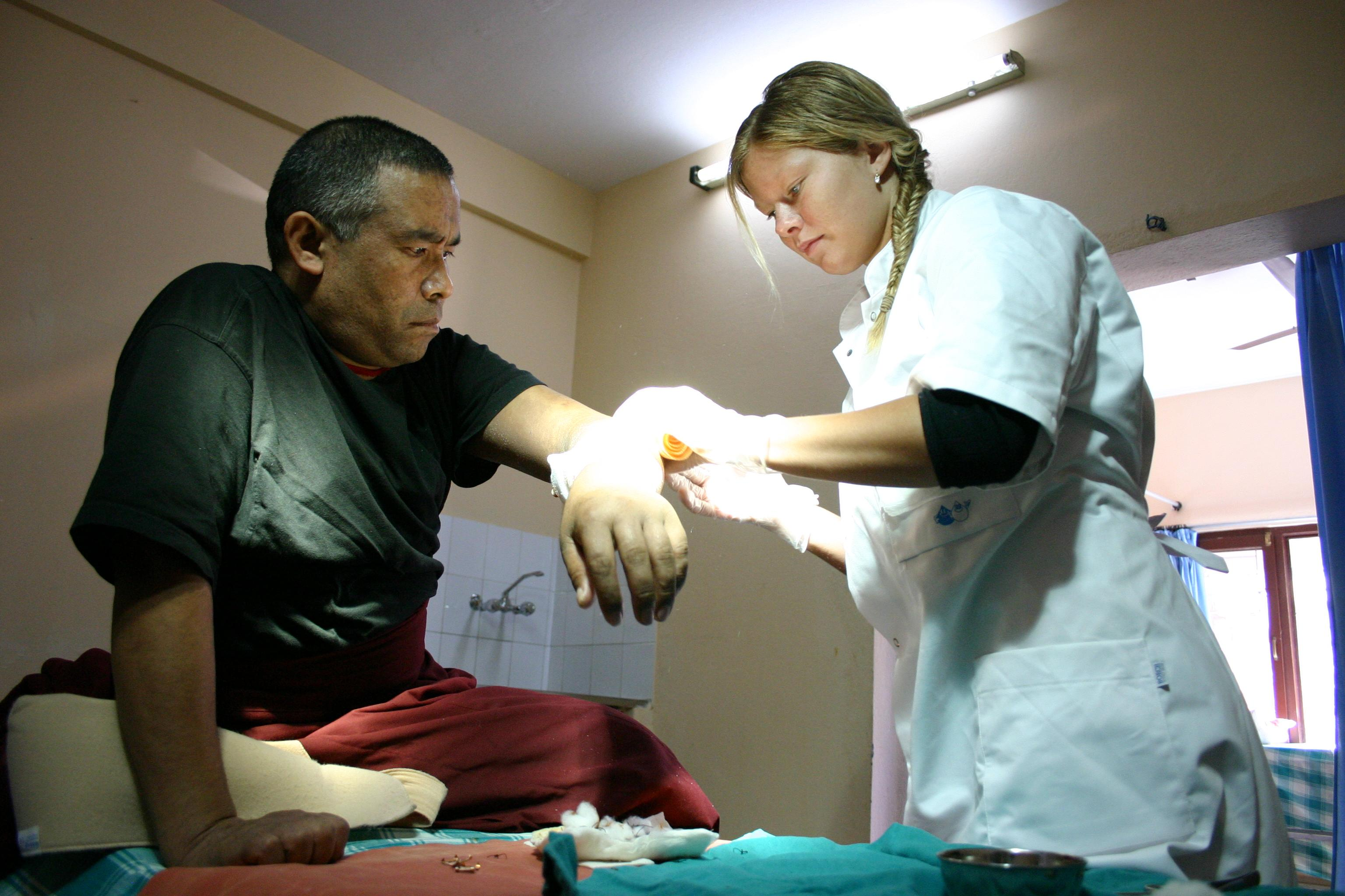 A female Projects Abroad intern is pictured cleaning a patients wound whilst on her medical internship in Nepal.